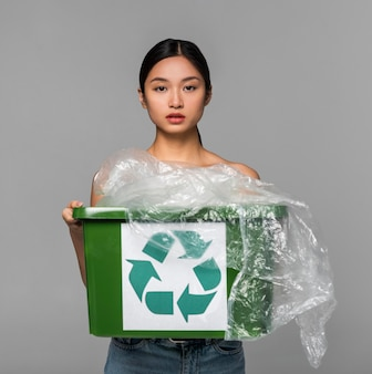 Portrait of woman holding a recycle bin
