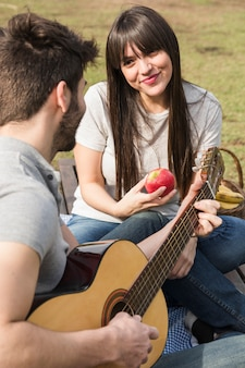 Portrait of woman holding red apple looking at her boyfriend playing guitar