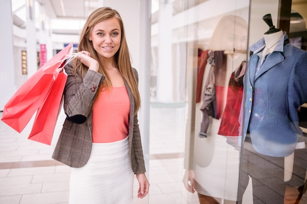 Portrait of woman holding shopping bags in mall
