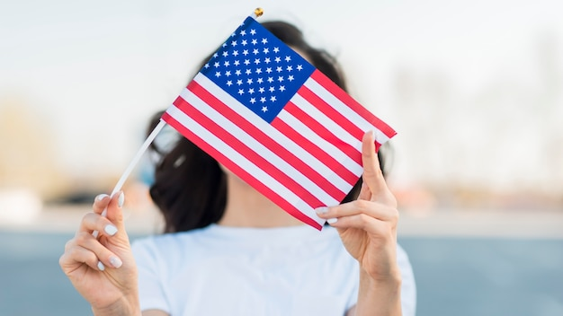 Portrait of woman holding usa flag over face