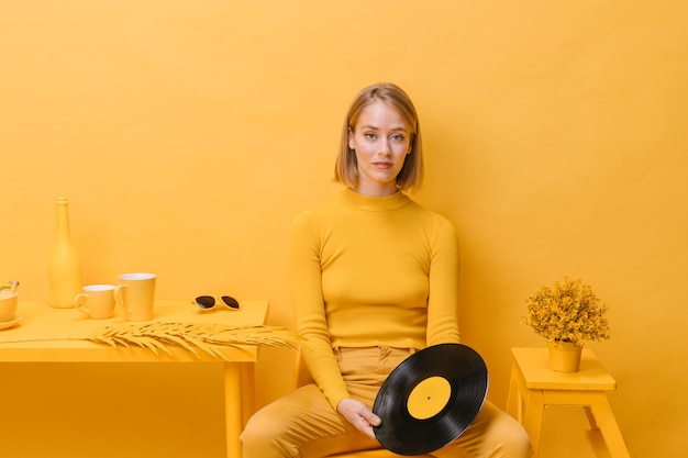 Portrait of woman holding a vinyl in a yellow scene