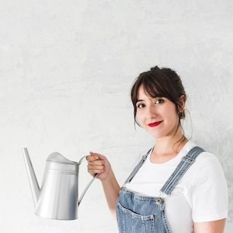 Portrait of a woman holding watering can in front of white background