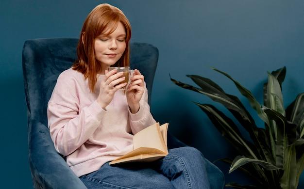 Ritratto di donna a casa a bere caffè e leggere