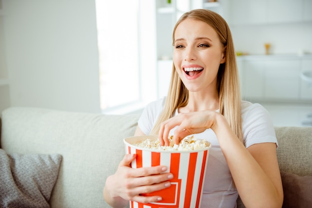 Portrait woman at home eating popcorn