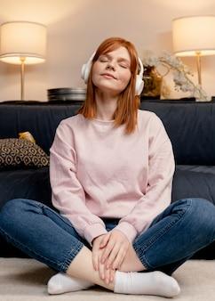 Donna del ritratto a casa ascoltando musica Foto Gratuite