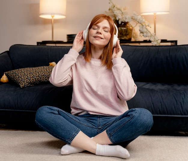 Portrait woman at home listening music