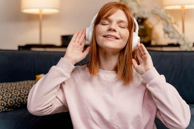 Donna del ritratto a casa ascoltando musica
