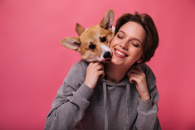 Portrait of woman in hoodie hugging her dog on pink background. cheerful lady in grey sweatshirt widely smiles and poses with corgi on isolated