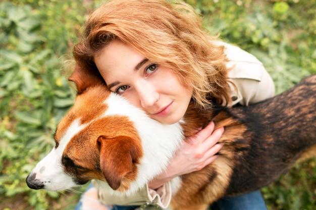Portrait of woman hugging her dog