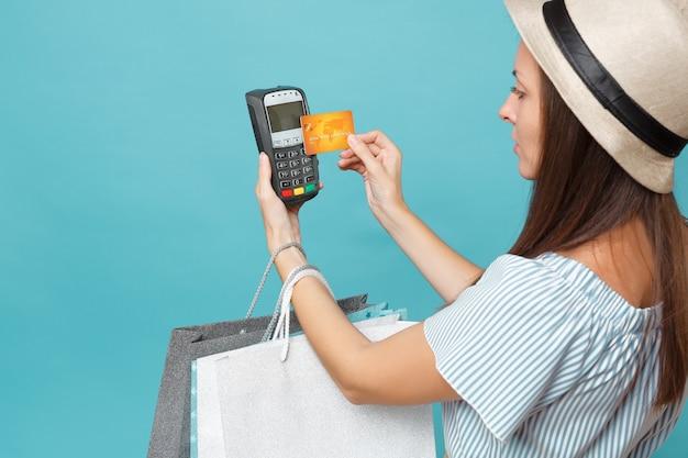 드레스를 입은 초상화 여성, 쇼핑 후 구매한 패키지 가방을 들고 있는 모자, 파란색 파스텔 배경에서 분리된 신용 카드 결제를 처리하고 획득하기 위한 무선 현대식 은행 결제 단말기.