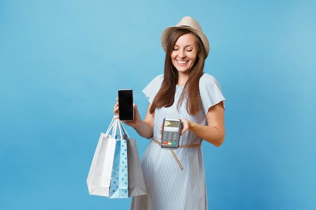 Портрет женщины в платье, шляпе, держащей пакеты с покупками после покупок, беспроводной современный банковский платежный терминал для обработки и получения платежей по кредитным картам, изолированных на синем пастельном фоне.