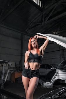 Портрет женщины в джинсах, шортах и топе, позирует рядом с автомобилем в гараже, на фоне старой машины.