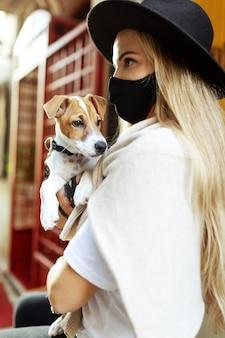 マスクの肖像画の女性は、ジャックラッセルの手に犬を保持します。コロナウイルス病covid-19新しい旅行の現実。医療マスクウォーキングの女の子。コロナウイルスのパンデミック予防策。家のペットと一緒に旅行する