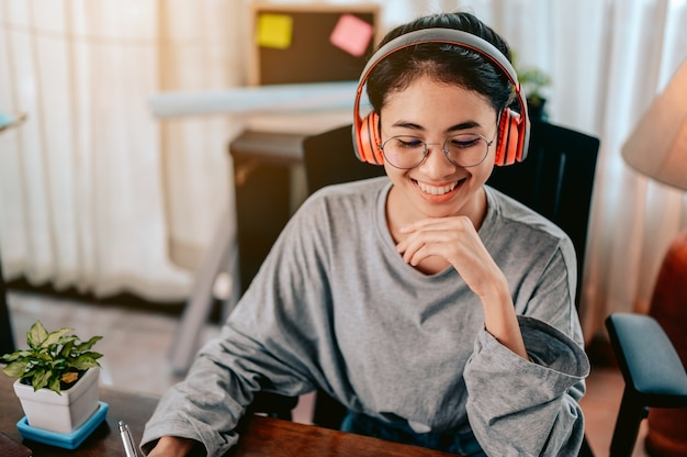 Portrait woman is working in the living room at home wearing headphones listening to music