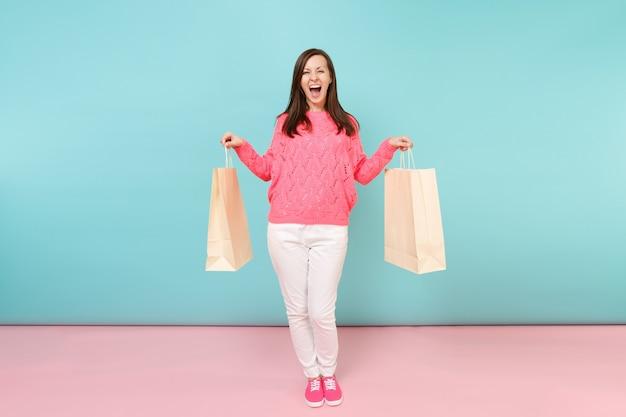 Ritratto di donna in maglia rosa maglione pantaloni bianchi che tengono i sacchetti multicolori con gli acquisti