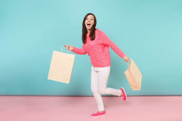 Portrait woman in knitted rose sweater white pants holding multi colored packages bags with purchases