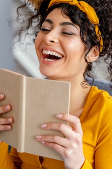 Portrait of woman laughing while reading book
