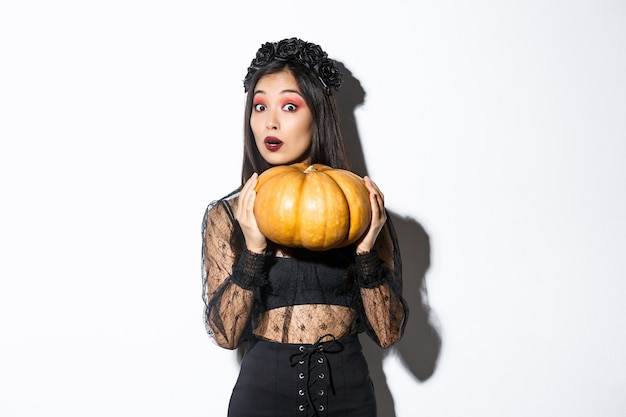 Portrait of woman lifting heavy pumpkin, getting ready for halloween