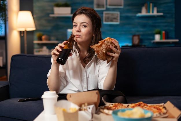 Ritratto di donna che guarda nella telecamera durante il pranzo di un fast food ordine del pasto rilassante sul divano