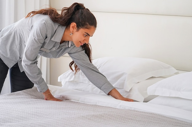 Portrait of woman maid making bed in hotel room