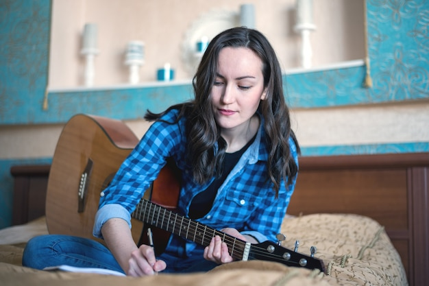 Portrait of a woman make music with an acoustic guitar writing ideas in a notebook