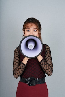 Portrait of woman making an announcement through the loudspeaker