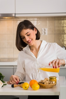 Portrait of woman making fresh orange juice