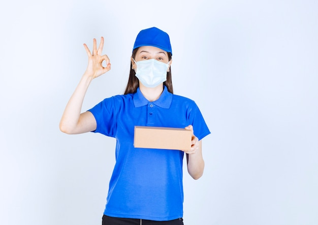 Portrait of woman in medical mask with paper box showing ok gesture