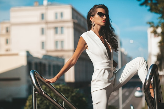 Portrait of woman model. woman in white suit posing on the street. fashion woman in sunglasses