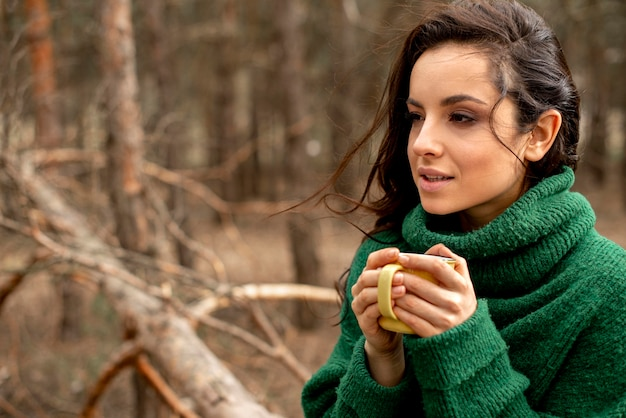 Portrait woman in nature enjoying tea