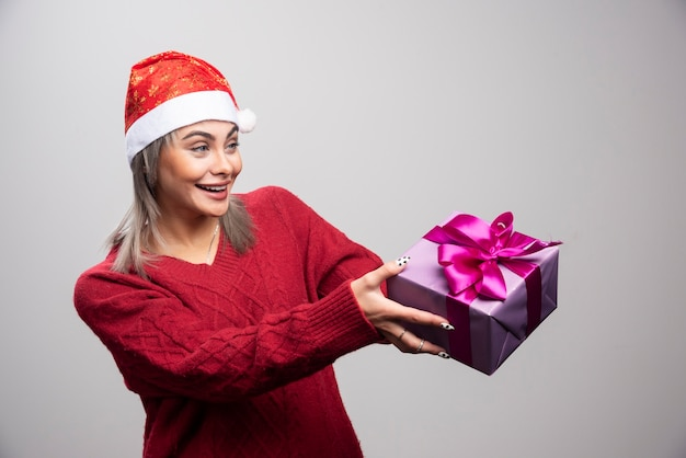 Portrait of woman offering gift box on gray background.