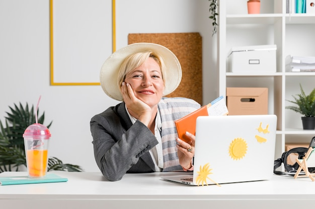 Portrait of woman in office prepared for summer holiday