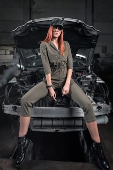 Portrait woman in overalls posing next to a  car in the garage, in background old car.creative industrial   portrait .design car workshop art concept