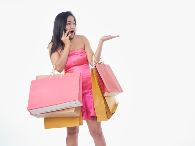 Portrait of woman in pink dress with shopping bags isolated on white background