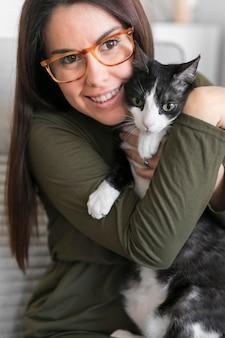 Ritratto di donna che gioca con il gatto seduto sulla sedia