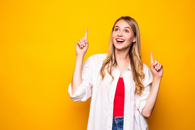 Portrait of woman pointing with two fingers and open mouth, isolated on yellow wall