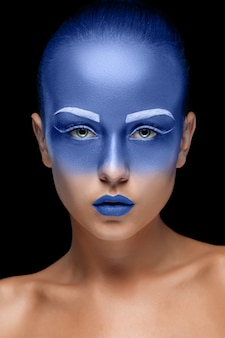 Portrait of a woman posing covered with blue paint