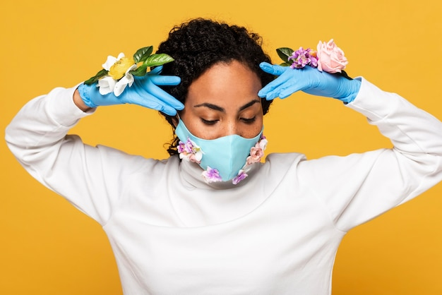 Portrait of woman posing with floral mask and gloves