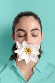 Portrait of woman posing with flower covering mouth