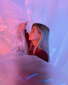 Портрет женщины позирует с пластиковой фольгой
