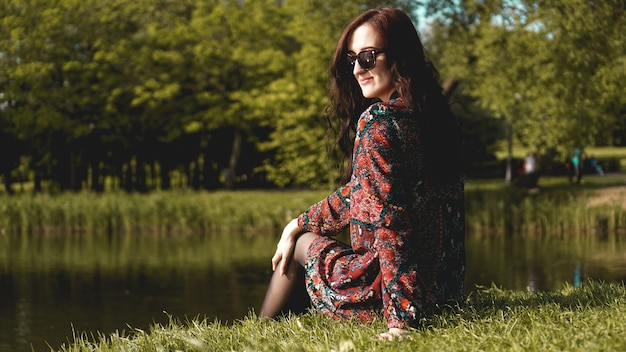 Portrait of woman in profile in sunglasses resting on the nature near the river.