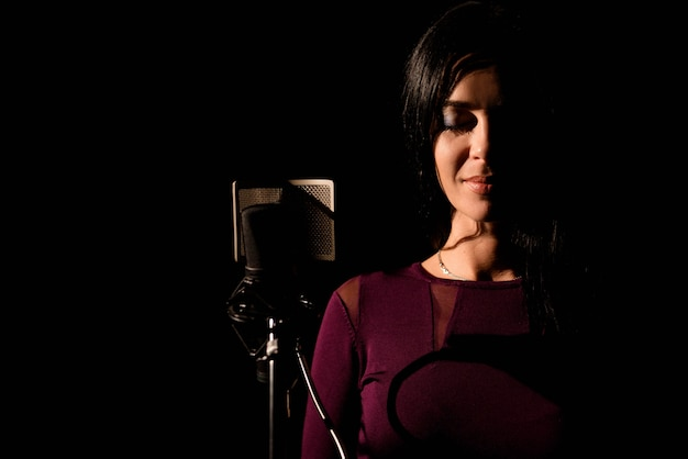 Portrait of woman recording a song in a professional studio