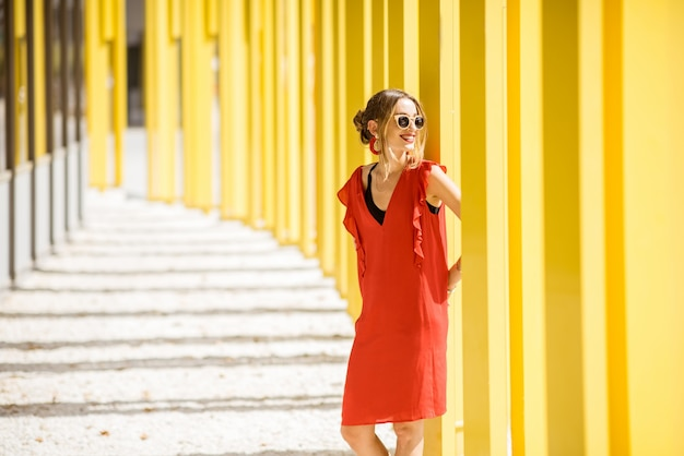 Portrait of a woman in red dress on the modern yellow building wall background. abstract geometric composition