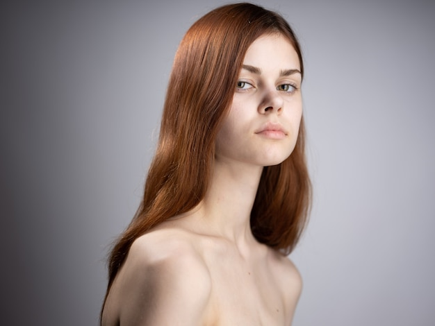 Portrait of a woman red hair naked shoulders side view