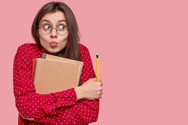 Ritratto di donna in camicia rossa e occhiali rotondi che tengono i blocchetti per appunti