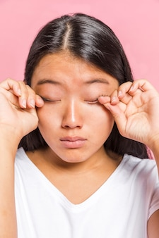 Portrait of woman rubbing her eyes