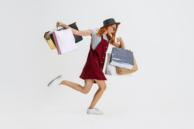 Portrait of woman running with many shopping bags isolated on white
