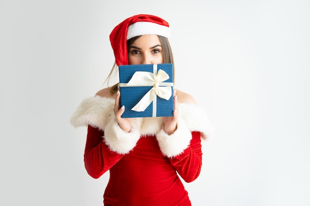 Portrait of woman in santa claus outfit hiding face behind box