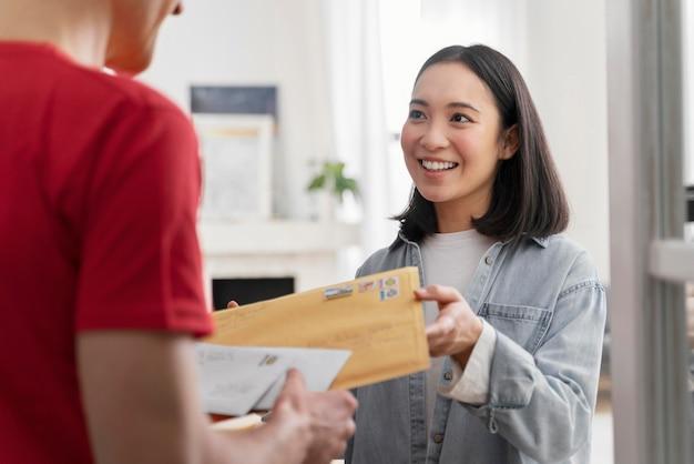 배달 서비스로 편지를 보내는 세로 여자