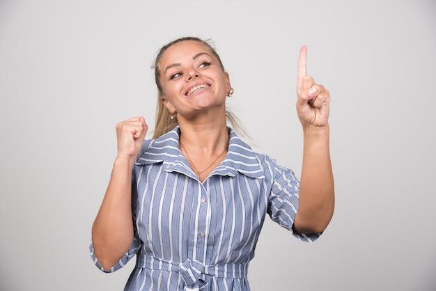 Ritratto di donna che mostra il dito sul muro grigio.